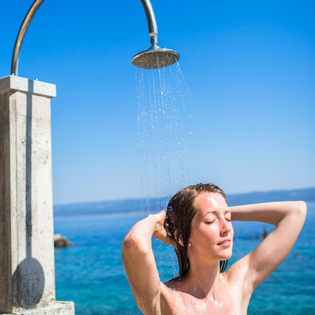 Pretty, young woman woman under shower on the beach photo