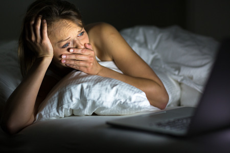 Pretty young woman watching something awful sad on her laptop in bed photo