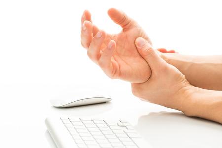 artrite: Lavorare troppo - soffre di una sindrome del tunnel carpale - giovane uomo che tiene il polso nel dolore a causa di un uso prolungato di tastiera e mouse su sfondo bianco