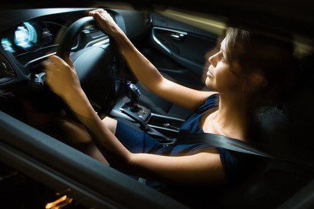 night stick: Driving a car at night - pretty, young woman driving her modern car at night, in a city