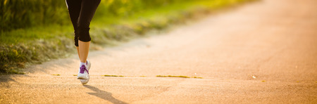 Detail of legs of a female runner on road