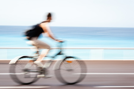 bike trail: Great way to get around in a city -Motion blurred cyclist going fast on a city bike lane Stock Photo