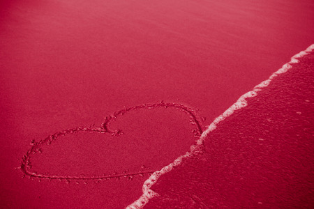 insincerity: Concept of infidelity or fragile fugitive ephemeral love  heart drawn in sand being washed by the sea