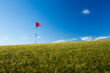 Red golf flag on a golf course, moving in the wind (motion blurred image); St. Andrews, Scotland photo
