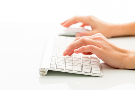 carpal: Hands of a person working an a keyboard over white background (color toned image; shallow DOF)