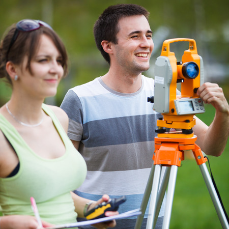 surveyors: Two young land surveyors at work