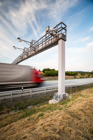 toll: truck passing through a toll gate on a highway