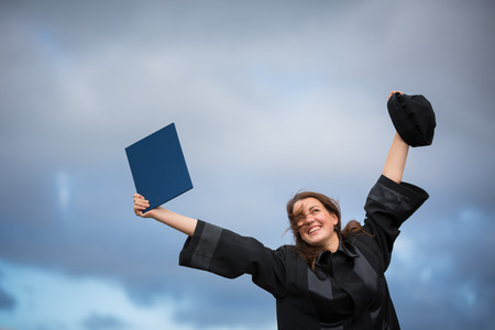 Pretty, young woman celebrating joyfully her graduation - spreading wide her arms, holding her diploma, savoring her success  photo