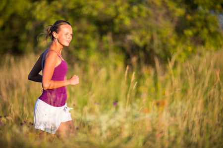 Young woman running outdoors on a lovely sunny day photo