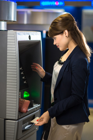 Pretty, young woman withdrawing money from her credit card in at an ATM  photo