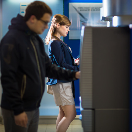 indebt: Pretty, young woman withdrawing money from her credit card in at an ATM Stock Photo