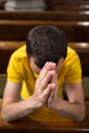 humility: Apuesto joven rezando en una iglesia