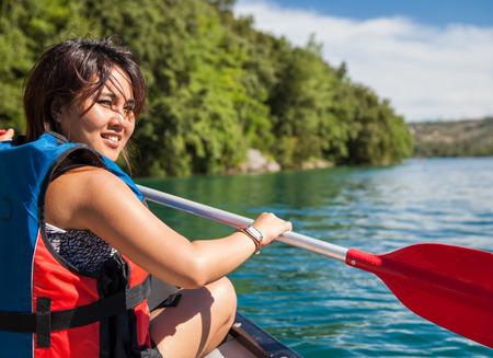 Mooie, jonge vrouw op een kano op een meer, peddelen, genieten van een mooie zomerdag