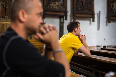 ハンサムな若い男は教会で祈る