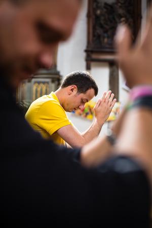 Knappe jonge man bidden in een kerk