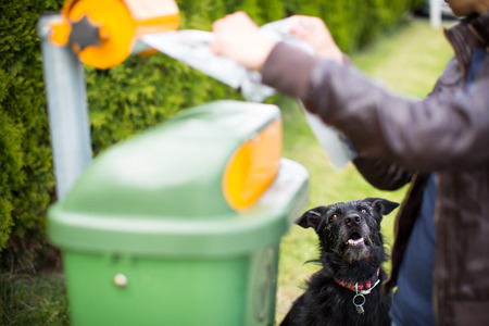 Do not let your dog faul! - Young woman grabbing a plastic bag in a park to tidy up after her dog later