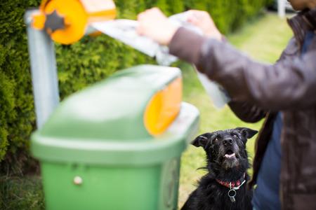 plastico pet: No deje que su perro faul! - Mujer joven agarrando una bolsa de plástico en un parque para poner en orden después de que su perro después Foto de archivo
