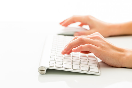 Hands of a person working an a keyboard over white background (color toned image; shallow DOF)