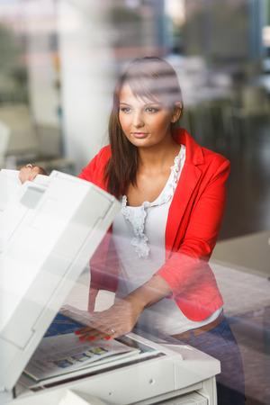 copy machine: Pretty young female college studentsecretary using a copy machine (shallow DOF; color toned image) Stock Photo