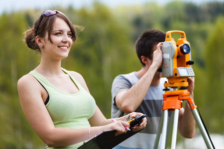 determine: Two young land surveyors at work