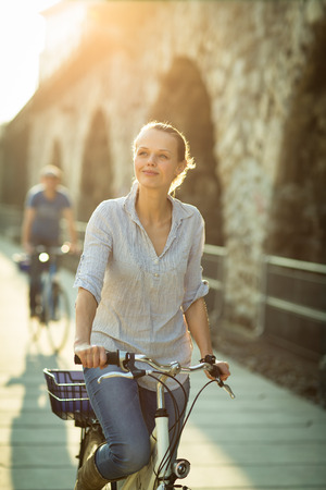 Pretty, young woman riding a bicycle in a city with her boyfriend (color toned image; shallow DOF) photo