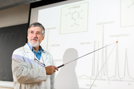Senior chemistry professor giving a lecture in front of classroom full of students (shallow DOF; color toned image) photo