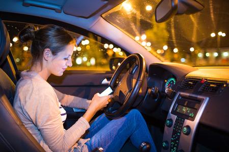 Jolie jeune femme utilise son téléphone intelligent tout en conduisant sa voiture dans la nuit