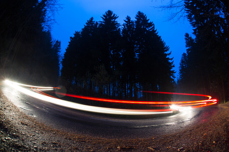 potentially: Cars going fast through a curve on a forest road at dusk, on a rainy day - i.e. Potentially dangerous driving conditions Stock Photo