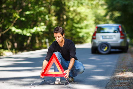 Handsome young man with his car broken down by the roadside, setting the safety triangle Stock Photo - 29820724