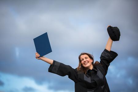 joyfully: Pretty, young woman celebrating joyfully her graduation