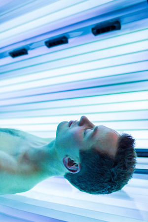 sunbed: Handsome young man relaxing during a tanning session in a modern solarium