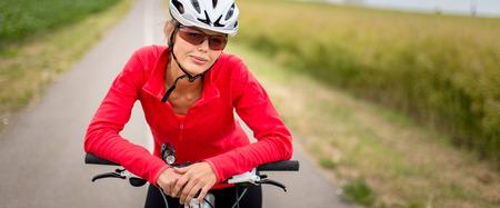mountain biker: Pretty, young female biker outdoors on her mountain bike (shallow DOF; selective focus)