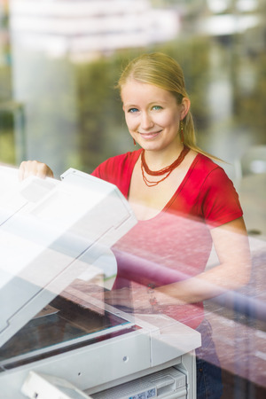copy machine: In the library - pretty, female student with using a copy machine (color toned image) Stock Photo