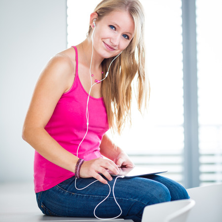 adulthood: Pretty, young female student listening to music on her tablet computer (color toned image)