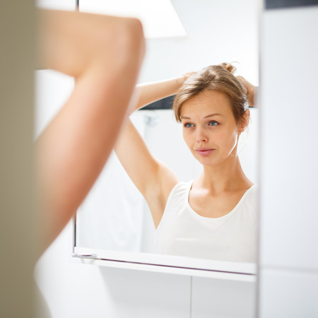 Pretty, young woman  in front of her bathroom during her morning routine (shallow DOF) photo