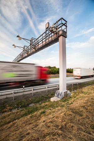 vrachtwagen passeren van een tolpoort op een snelweg (beweging wazig beeld, kleur getinte afbeelding)