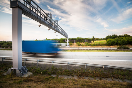 toll: Truck passing through a toll gate on a highway (motion blurred image; color toned image) Stock Photo