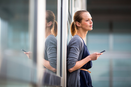 sleek: Portrait of a sleek young woman calling on a smartphone and using her laptop in a an urbancity context (shallow DOF; color toned image)
