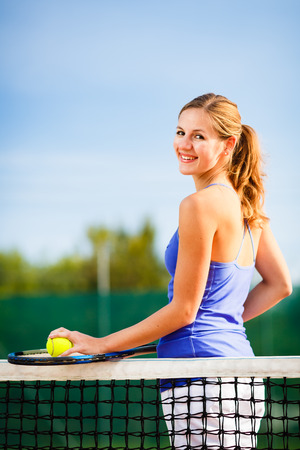 Portrait of a pretty, young tennis player  on  a court on a lovely summer day photo