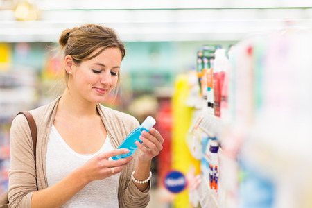 Beautiful young woman shopping for cosmetics in a grocery storesupermarket (color toned image) Imagens