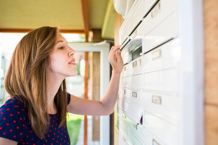 correspondencia: Mujer bonita, joven que controla su buzón para cartas nuevas