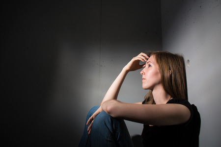 Young woman suffering from a severe depression (very harsh lighting is used on this shot to underlineconvey the gloomy mood of the scene)