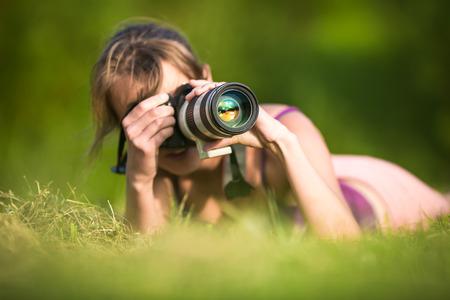 El fotógrafo femenina bonita tumbado en la hierba, en un hermoso día de verano, tomar fotos con su cámara réflex digital y un teleobjetivo