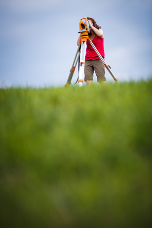 cartographer: Young, female land surveyor at work - using the theodolite level outdoors