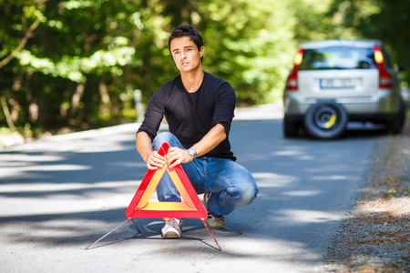 gass: Handsome young man with his car broken down by the roadside, setting the safety triangle Stock Photo