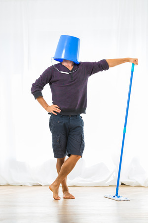 Young man mopping the floor. Or is he? Stock Photo - 30159587