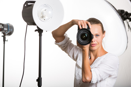 female photographer: Pretty, female pro photographer with digital camera - DSLR and a huge telephoto lens in her well equiped studio, taking photos (color toned image; shallow DOF)