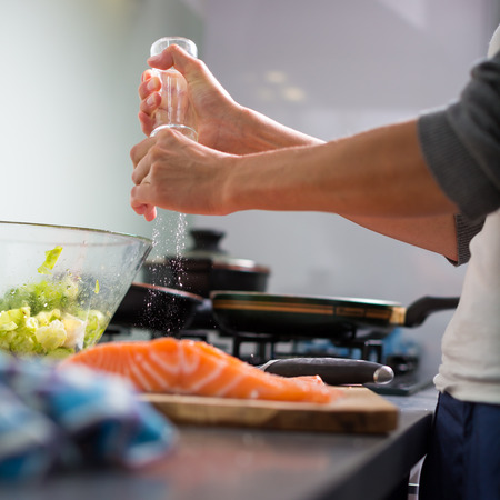 Young woman seasoning a salomn filet in her modern kitchen, preaparing a healthy food photo