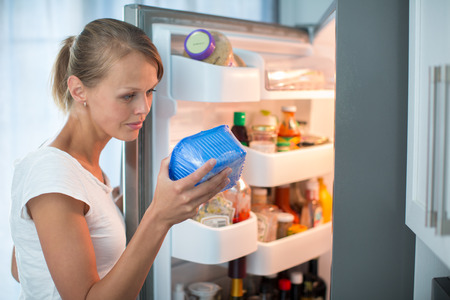 breakfast food: Is this still fine? Pretty, young woman in her kitchen by the fridge, looking at the expiry date of a product she took from her fridge -