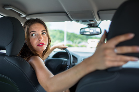 Young, woman driving a car, going home from work Stock Photo
